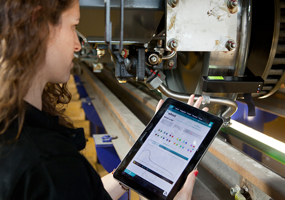 A worker inspects a train with her tablet